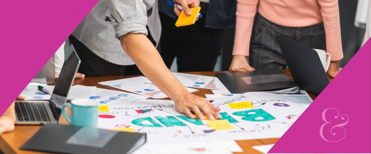 "People are standing and working around a table. There are sticky-notes, computers, books and posters. A poster says ""brand."""