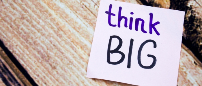 "A purple note sits in front of a wooden background. The note's text says ""think big."""