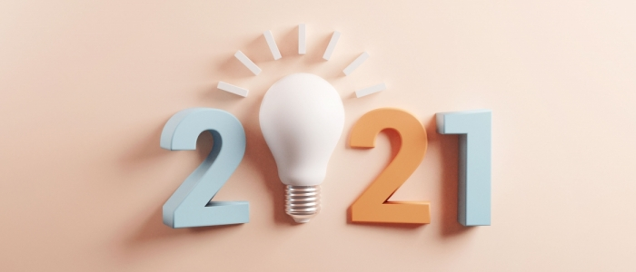 Text reads 2021 in front of a pink background. The 0 is a lightbulb.