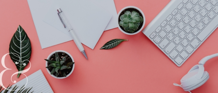 Dark green plants, office supplies, and a keyboard and headphones sit on top of a pink desk. A white ampersand is in the bottom left corner.