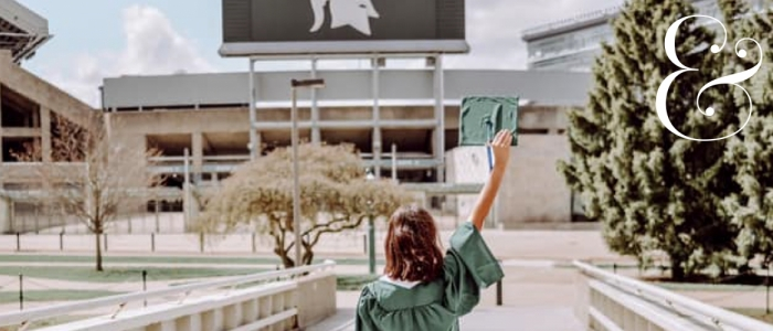 Image features a student in a green cap and gown in front of the MSU football stadium.