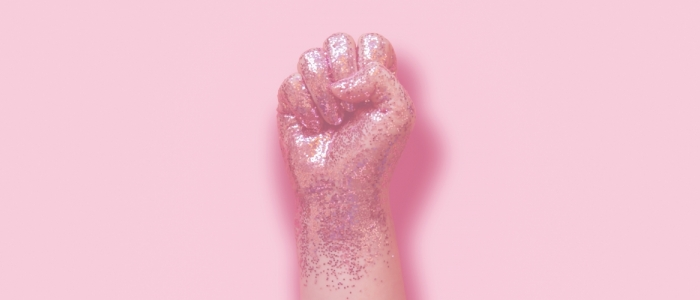A pink, glittery fist is in front of a pale pink background.